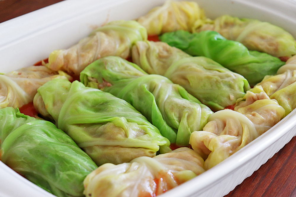 Placing the cabbage rolls in a single layer in an oven safe baking pan