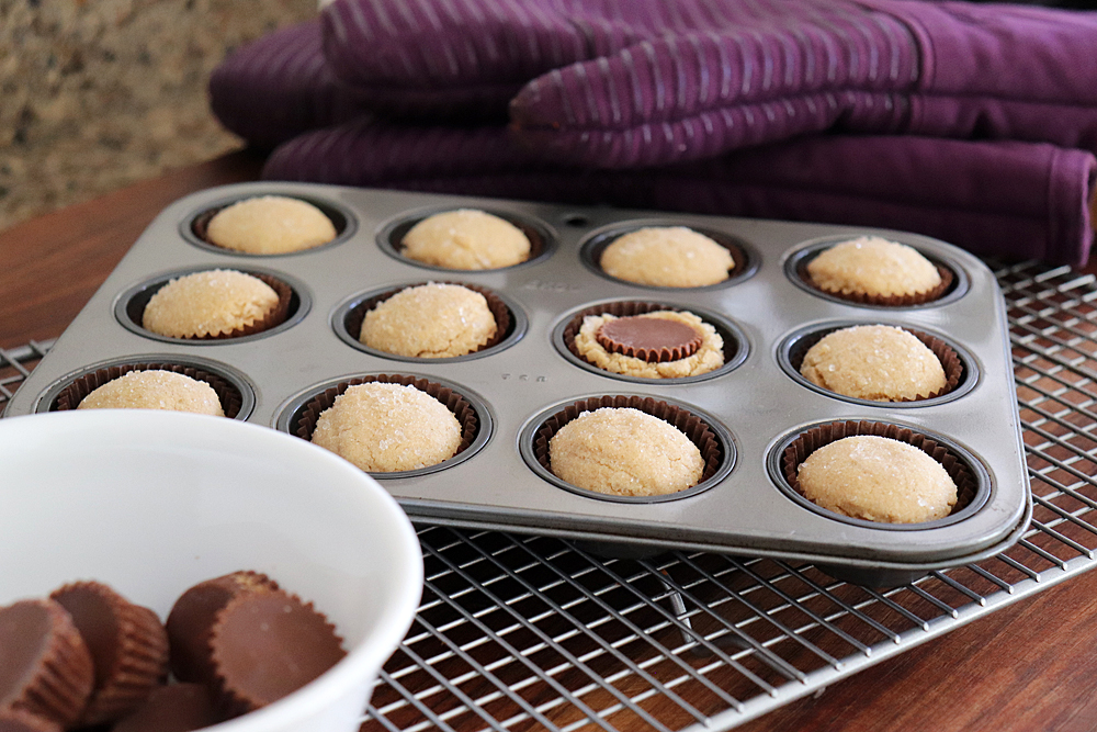 Pressing Reese's Miniatures into the baked peanut butter cookies
